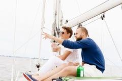 Amis heureux s'asseyant ensemble sur une plate-forme d'un yacht et d'un boire Photos stock