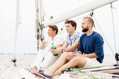 Amis heureux s'asseyant ensemble sur une plate-forme d'un yacht et d'un boire Images stock