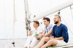 Amis heureux s'asseyant ensemble sur une plate-forme d'un yacht et d'un boire Images libres de droits
