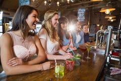 Amis heureux s'asseyant par des boissons sur le compteur Photographie stock