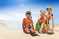 Amis heureux s'asseyant sur la plage sablonneuse dans le masque de scaphandre Photographie stock
