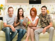 Amis heureux s'asseyant sur le divan Photos libres de droits