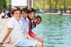 Amis heureux s'asseyant sur le remblai de rivière Image stock