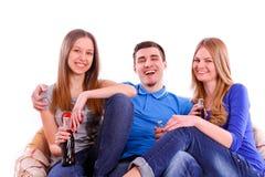 Amis heureux s'asseyant sur le sofa et la soude potable Photos stock