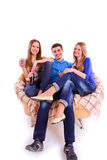 amis heureux s'asseyant sur un sofa et une soude potable Photos stock