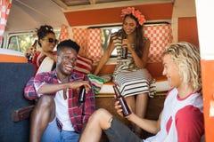 Amis heureux s'asseyant tout en tenant des bouteilles à bière dans le camping-car Image stock