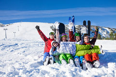 Amis heureux s'asseyants avec des surfs des neiges ayant l'amusement Photo stock