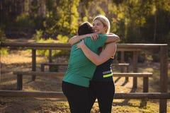 Amis heureux s'embrassant pendant le parcours du combattant Image libre de droits