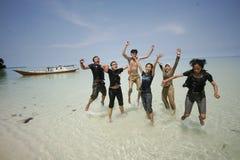 Amis heureux sautant à la belle plage Photo stock