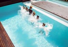 Amis heureux sautant dans la piscine Images stock