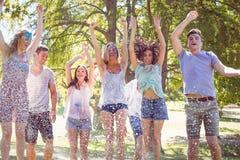 Amis heureux sautant dans la pousse de l'eau Image stock