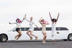Amis heureux sautant devant une limousine Photo stock