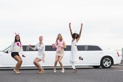 Amis heureux sautant devant une limousine Images stock