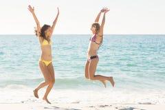 Amis heureux sautant ensemble Photographie stock