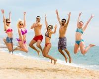 Amis heureux sautant près de la mer Photos stock