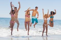 Amis heureux sautant sur la plage Photographie stock libre de droits