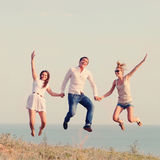 Amis heureux sautant sur la plage Photo libre de droits
