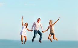 Amis heureux sautant sur la plage Photographie stock
