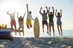 Amis heureux sautant sur le rivage à la plage Photographie stock libre de droits