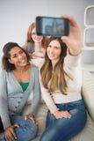 Amis heureux se photographiant avec le smartphone Photos stock