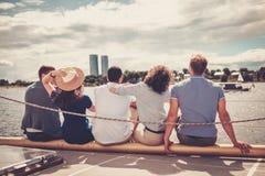 Amis heureux se reposant sur un yacht Photos libres de droits