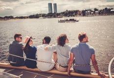Amis heureux se reposant sur un yacht Images stock