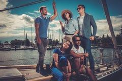 Amis heureux se reposant sur un yacht Image stock