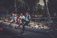 Amis heureux se reposant sur un yacht Photographie stock libre de droits