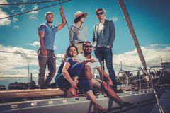 Amis heureux se reposant sur un yacht Photos stock