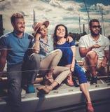 Amis heureux se reposant sur un yacht Photographie stock