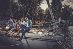 Amis heureux se reposant sur un yacht Photo libre de droits