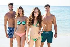 Amis heureux se tenant à la plage Images stock