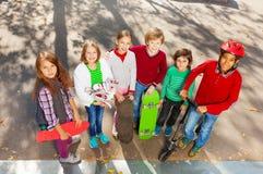 Amis heureux se tenant étroits avec des planches à roulettes Image stock