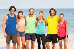 Amis heureux se tenant avec le bras autour à la plage Images libres de droits