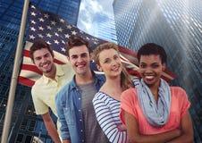 Amis heureux se tenant dans une rangée contre le drapeau américain Image stock