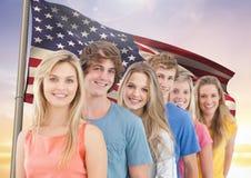 Amis heureux se tenant dans une rangée contre le drapeau américain Images libres de droits
