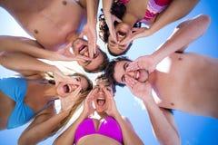 Amis heureux se tenant en cercle et cris Image libre de droits