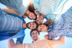 Amis heureux se tenant en cercle et regardant l'appareil-photo Photographie stock