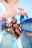 Amis heureux se tenant en cercle et regardant l'appareil-photo Image stock