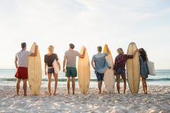 Amis heureux se tenant en conformité avec des planches de surf Image libre de droits
