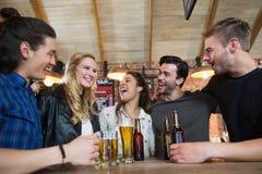 Amis heureux se tenant prêt le verre et les bouteilles de bière sur la table Photographie stock