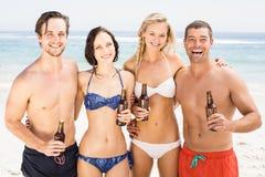 Amis heureux se tenant sur la plage avec des bouteilles à bière Image stock