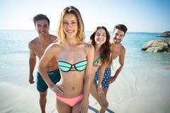 Amis heureux se tenant sur le rivage à la plage Image stock