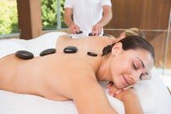 Amis heureux se trouvant sur des tables de massage avec les pierres chaudes sur leurs dos Image stock