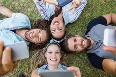 Amis heureux se trouvant sur l'herbe Photos libres de droits