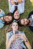 Amis heureux se trouvant sur l'herbe Image stock