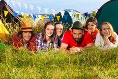 Amis heureux se trouvant sur l'herbe au terrain de camping Image stock