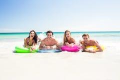 Amis heureux se trouvant sur le matelas gonflable au-dessus de l'eau Photographie stock