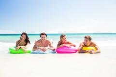 Amis heureux se trouvant sur le matelas gonflable au-dessus de l'eau Image libre de droits