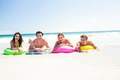 Amis heureux se trouvant sur le matelas gonflable au-dessus de l'eau Images libres de droits